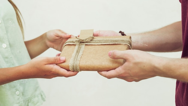 Close-up of couple's hand holding gift in front of plain background