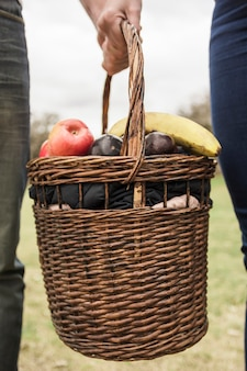 Close-up of couple's hand holding picnic basket full of fruits