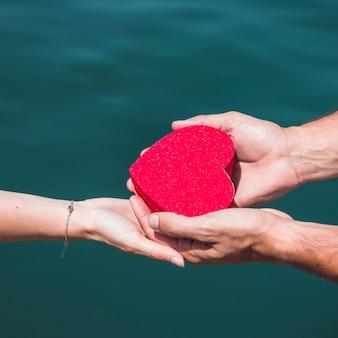 Primo piano della mano di una coppia che tiene a forma di cuore rosso davanti al mare