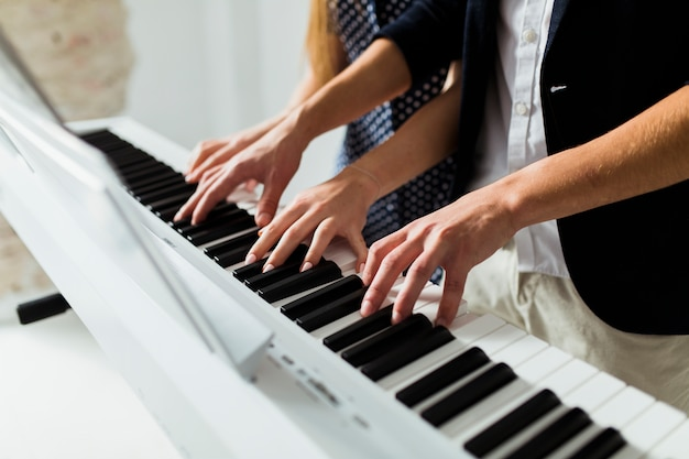 Close-up of couple's hand playing piano keyboard