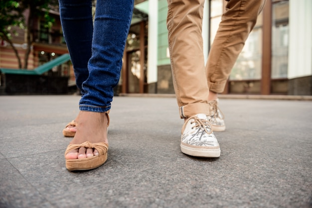 Close up of couple's legs in keds walking down street.