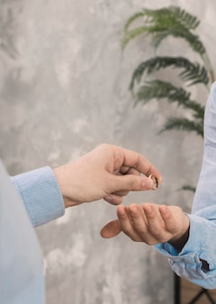 Close-up couple taking wedding rings off Free Photo