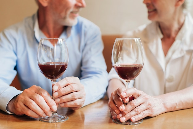 Close-up couple with glasses of red wine