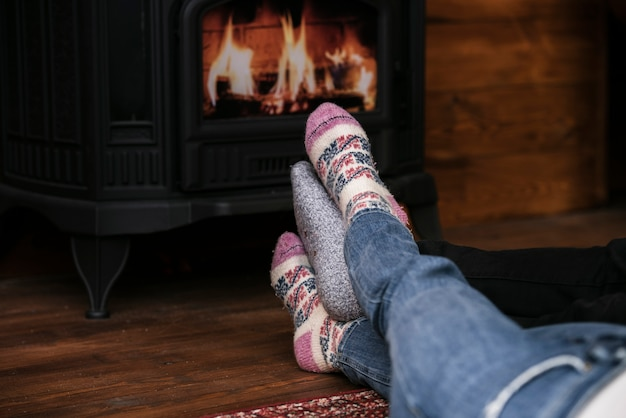 Close-up couples feet next to fireplace