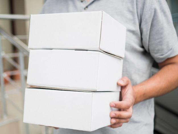 Крупный план курьер держит коробки