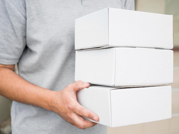 Corriere del primo piano che tiene le scatole bianche