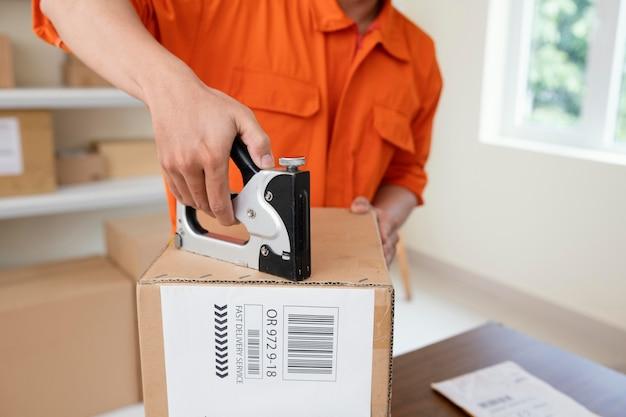 Primo piano sul corriere che prepara il pacco per la consegna