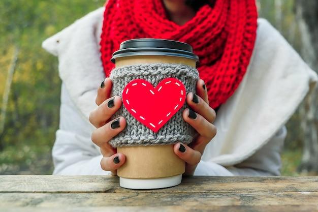 자연에 손에 하트 모양으로 아늑한 컵을 닫습니다. 야외 피크닉 좋은 분위기