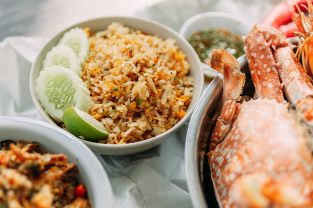 Close-up crab fried rice with cucumber and lime and steamed flower crabs served with thai style spicy seafood sauce.