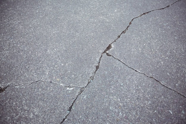 Close-up of cracked asphalt road background