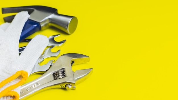 Close up of craftsman tools on a yellow background, hammer, wrench, mechanic gloves, top view