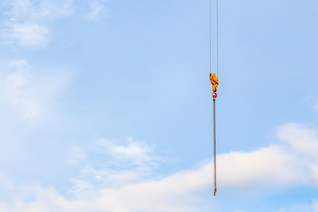 Close up crane with a hook on the end in the blue sky