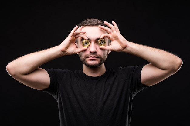 Close up of a crazy entrepreneur with bitcoins in his eyes pointing fingers isolated over black