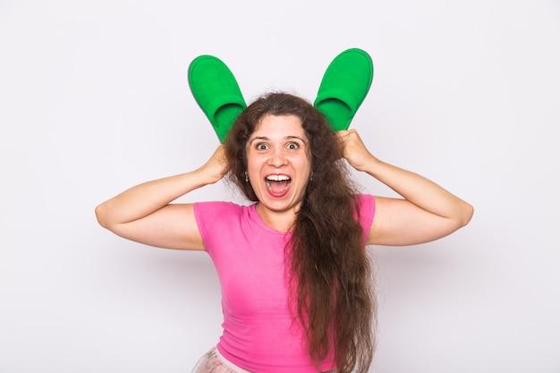 여자의 미친 우스꽝스러운 초상화를 닫고, 찡그린 얼굴을 하고, 흰색 배경 위에 슬리퍼로 토끼 귀를 모방