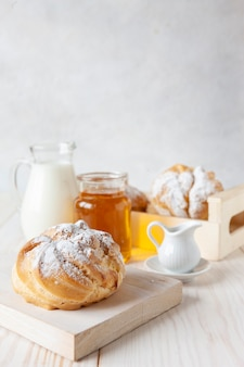 Close-up of cream buns, bottle of milk and honey