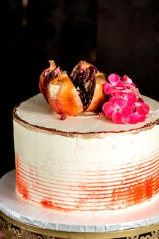 Close up of creamy cake garnished with pomegranate and flowers