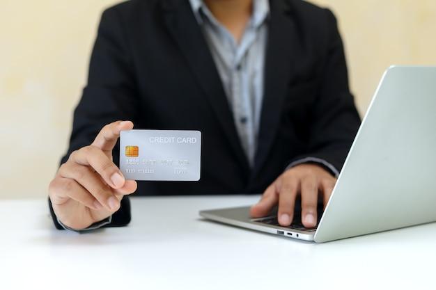 Закройте вверх по кредитной карте в руке бизнесмена, используя концепцию ноутбука, покупки и оплаты.