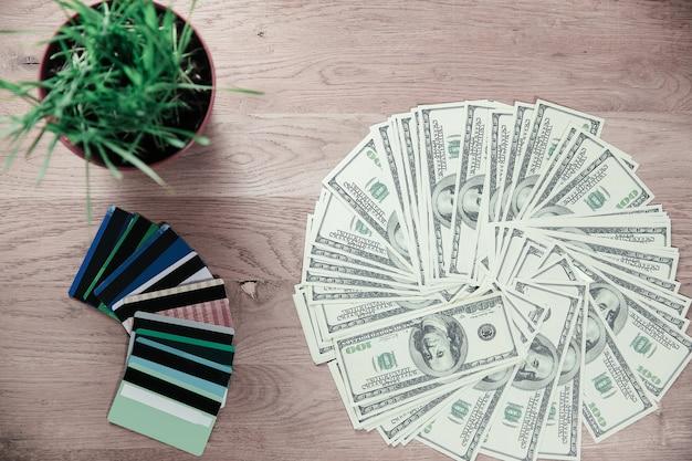 닫습니다.신용 카드와 달러 지폐는 나무 테이블에 놓여 있습니다.