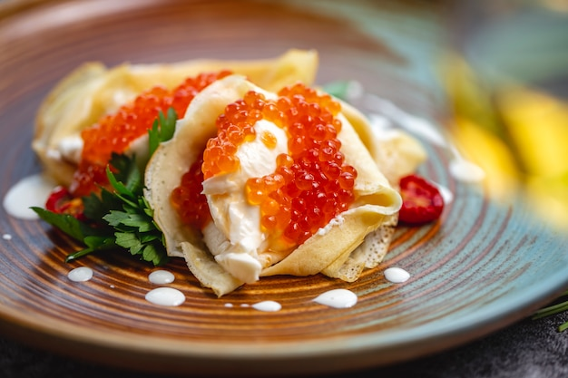Close up of crepes with red caviar and cream garnished with parsley