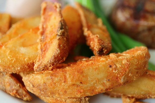 Close-up of crispy fried potatoes with blurry vegetables and steak in background