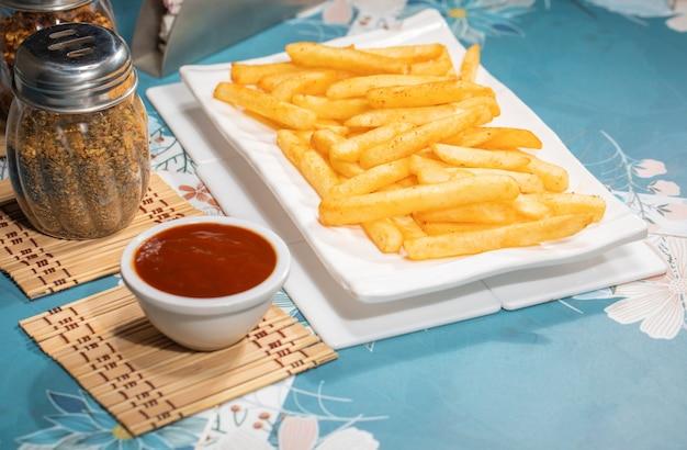 소박한 나무 테이블에 제공되는 두 개의 디핑 소스와 함께 하얀 접시에 바삭한 감자 튀김을 닫습니다