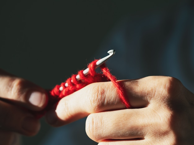 Крупный план вязания крючком красной шерстяной пряжи на темном фоне.