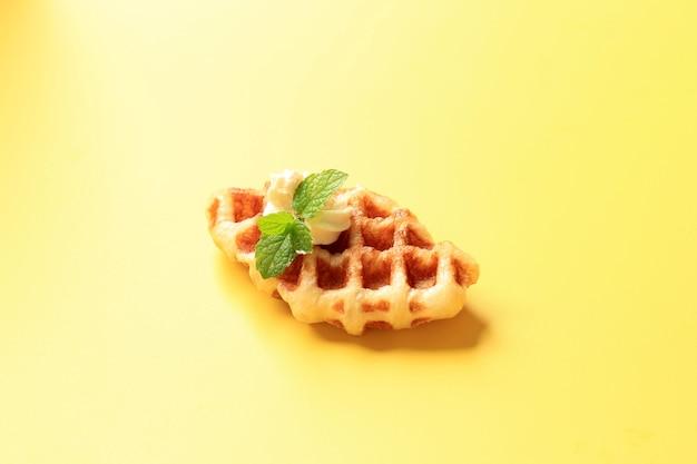 黄色の背景に分離された上にクリームチーズとクロワッサンワッフル(クロワッフル)を閉じる