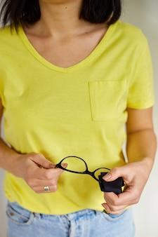 Закройте руки женщины, вытирая модные черные линзы очков полотенцем, черной тканью из микрофибры, женщиной в желтых футболках и джинсах, копией пространства. концепция здравоохранения, зрения и медицины