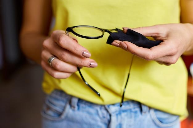 トレンディな黒いメガネレンズをタオル、黒いマイクロファイバー組織で拭く女性の作物の手をクローズアップ