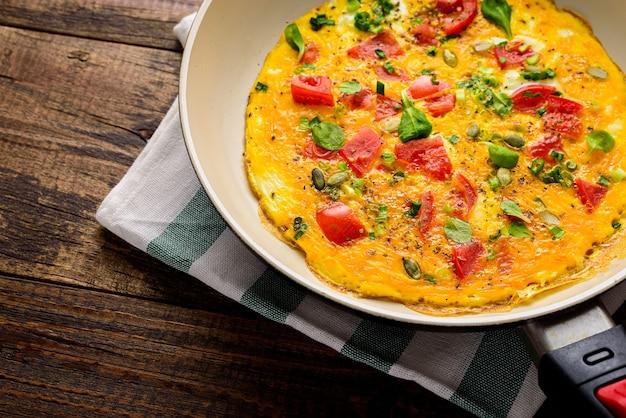 茶色の木製の背景にフライパンでトマトとほうれん草と作物のオムレツを閉じます。素朴な朝食のコンセプト