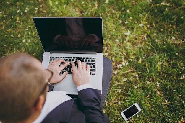 古典的なスーツでトリミングされたビジネスマンを閉じます。男は柔らかいプーフに座って、自然の屋外の緑の芝生の都市公園でラップトップpcコンピューターに取り組んでいます。モバイルオフィス、ビジネスコンセプト。上面図。スペースをコピーします。
