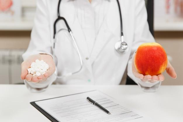 책상에 앉아 있는 잘린 여의사를 닫고, 손바닥에 흰색 알약이 든 병을 들고, 병원의 가벼운 사무실에 빨간 사과를 들고