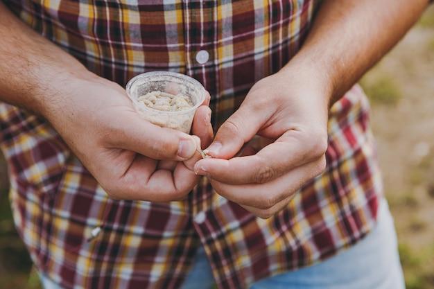 체크 무늬 셔츠를 입은 잘린 어부를 손에 쥐고 구더기가 있는 작은 흰색 상자를 잡고 낚싯대로 물고기에 미끼를 끼웁니다. 남자는 낚시를 위해 벌레를 잡고 있습니다. 라이프 스타일, 레크리에이션, 레저 개념