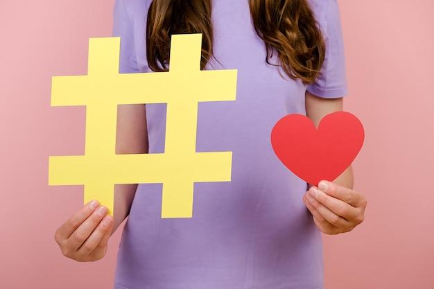 티셔츠를 입은 젊은 여성의 클로즈업 영상은 큰 노란색 해시태그 기호와 작은 빨간 하트를 보여주며, 인터넷에서 자선의 상징인 스튜디오에서 분홍색 배경 위에 고립된 포즈를 취합니다.