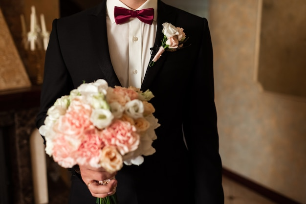 Close-up of a cropped frame is a tender bouquet of roses in the hands of a groom.
