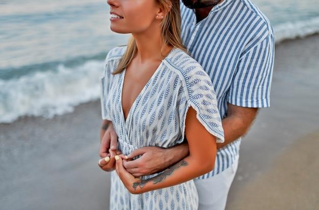 Обрезанное изображение крупным планом молодая влюбленная пара обнимается на берегу моря, наслаждается друг другом и отпуском, романтически проводит время на пляже.