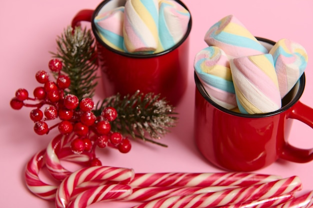 Close-up, cropped image of christmas items, striped sugary candy canes, holly and mug with hot drink and wet colorful marshmallows on pink colored background with copy space for christmas ad
