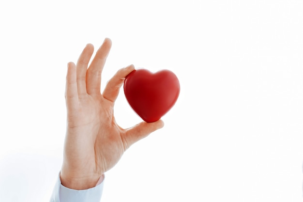 Close-up . cropped image of a doctor showing a small red heart . concept of health protection.