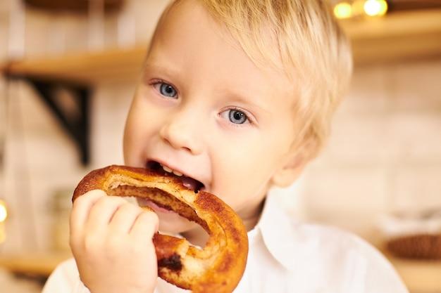 ブロンドの髪と青い目が口を開けてサクサクのベーグルを噛み、楽しい表情をしている白人の男の子のトリミングされた画像をクローズアップします。子供の頃、食品、ケア、健康の概念