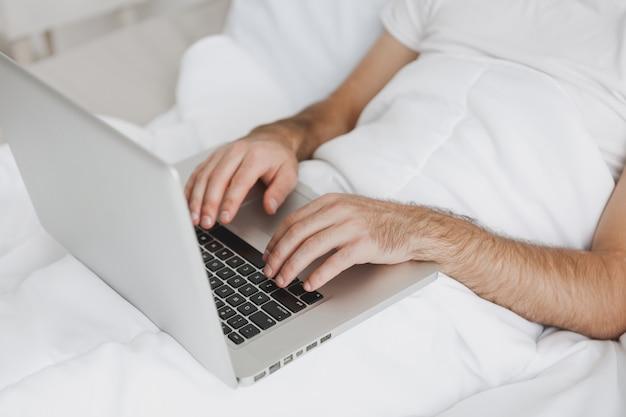Крупным планом обрезанное изображение человека, лежащего в постели с белым одеялом в спальне у себя дома