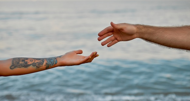 海と互いに向かって伸びる波に対する若いカップルの手のクローズアップトリミング画像。