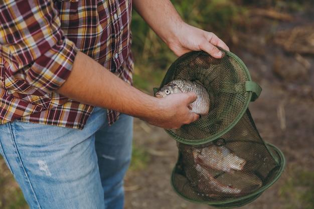 소매를 걷어붙인 체크 무늬 셔츠를 입은 잘린 남자가 물고기를 잡고 흐릿한 배경의 호수 기슭에 있는 녹색 낚시 격자에 넣습니다. 라이프 스타일, 레크리에이션, 어부의 레저 개념