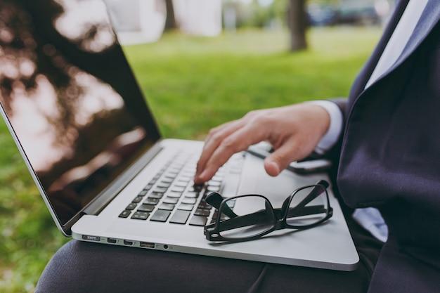 키보드에서 자른 손을 닫습니다. 클래식 정장, 안경 사업가입니다. 남자는 부드러운 푸프에 앉아 야외 녹색 잔디밭에 있는 도시 공원에 있는 노트북 컴퓨터에서 일합니다. 모바일 오피스 개념입니다. 측면보기.