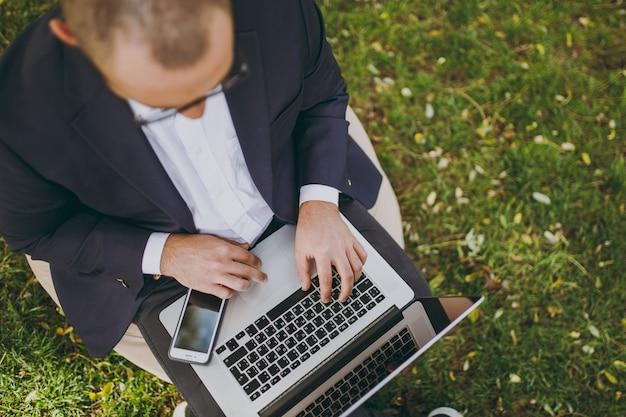 キーボードの手を切り取ってクローズアップします。古典的なスーツ、眼鏡のビジネスマン。男は柔らかいプーフに座って、屋外の緑の芝生の都市公園でラップトップpcコンピューターで作業します。モバイルオフィスのコンセプト。上面図。