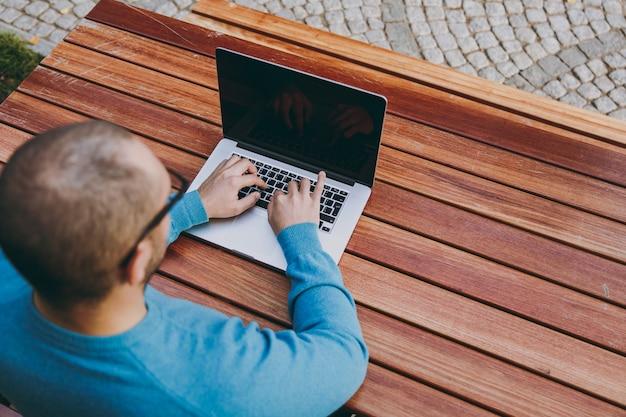 Закройте вверх обрезанного успешного бизнесмена умного человека или студента, сидящего за столом с мобильным телефоном в городском парке, используя ноутбук, работая на открытом воздухе. концепция мобильного офиса. руки на клавиатуре. вид сверху.