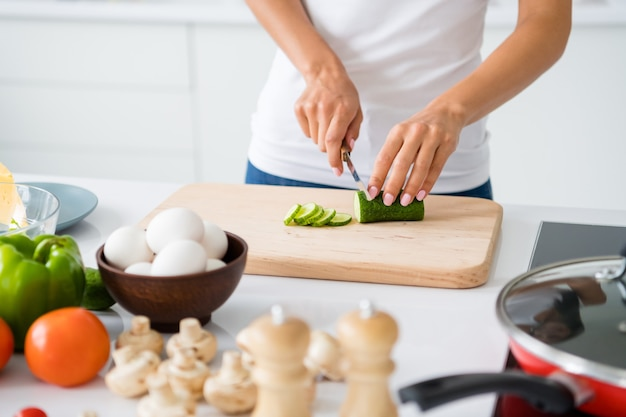 Close up cropped photo of joyful housewife prepare feast for her veggie family cutting green organic cucumber on chopping board in kitchen white house indoors
