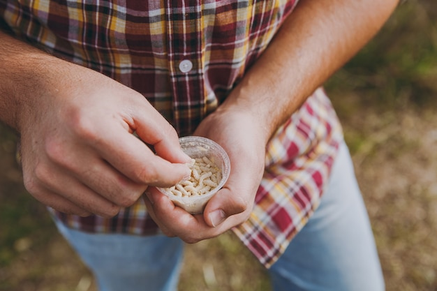 체크 무늬 셔츠를 입은 어부의 자른 사진을 클로즈업하면 구더기가 든 작은 흰색 상자, 물고기 미끼가 손에 들어 있습니다. 남자는 낚시를 위해 벌레를 잡고 있습니다. 라이프 스타일, 레크리에이션, 레저 개념입니다.