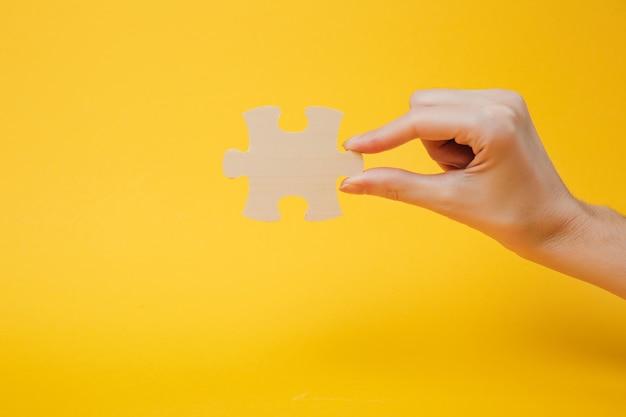 Закройте вверх по обрезанной фотографии руки, держащей кусок деревянной головоломки, изолированной на ярко-желтом стенном фоне. концепция ассоциации и связи. скопируйте космический рекламный макет.