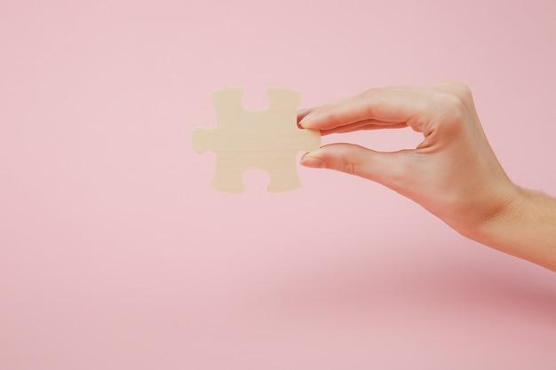 Закройте вверх по обрезанной фотографии руки, держащей кусок деревянной головоломки, изолированной на пастельных розовых стенах. концепция ассоциации и связи. скопируйте космический рекламный макет.