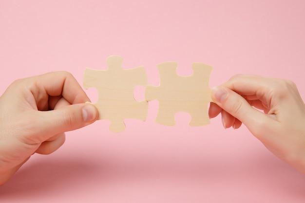 Закройте обрезанное фото рук, держащихся, пытаясь соединить пару деревянных частей головоломки, изолированных на пастельных розовых стенах. ассоциация, концепция связи. скопируйте космический рекламный макет.